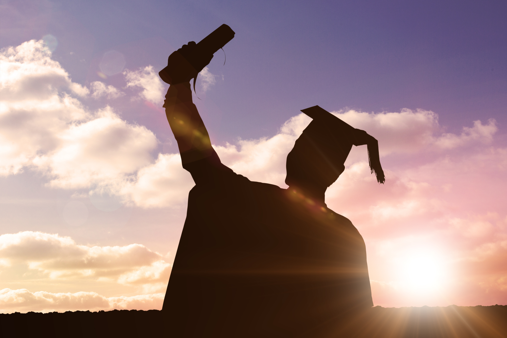 The sunset casts a silhouette of a college student wearing a cap and gown, raising their diploma into the air.