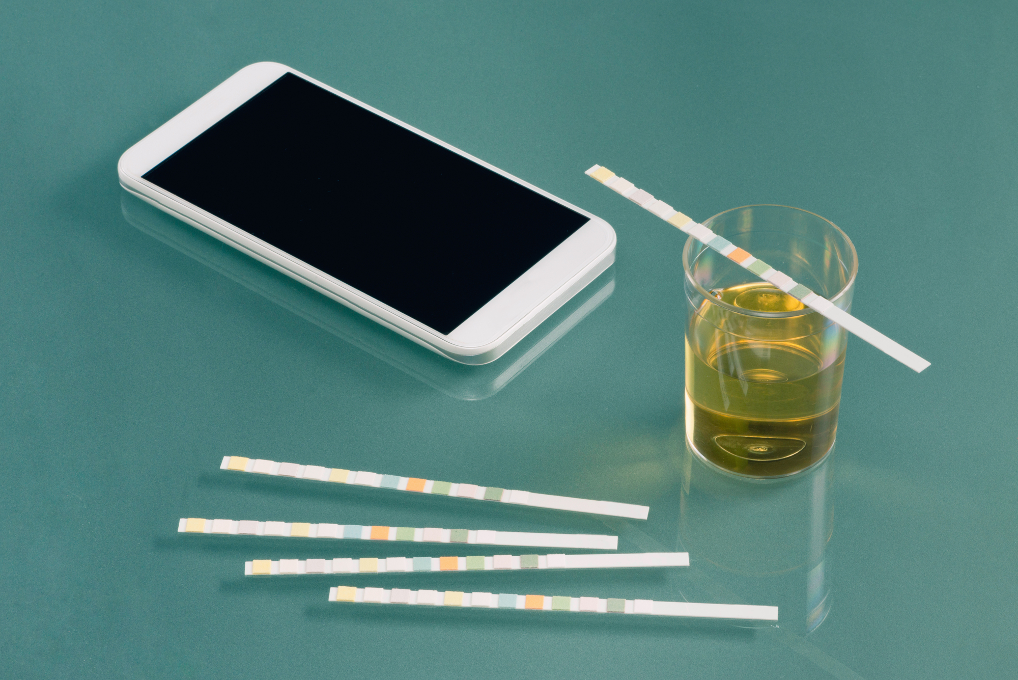 A smartphone sitting on a green tabletop next to a small glass containing a urine sample, with paper drug test strips laying nearby.