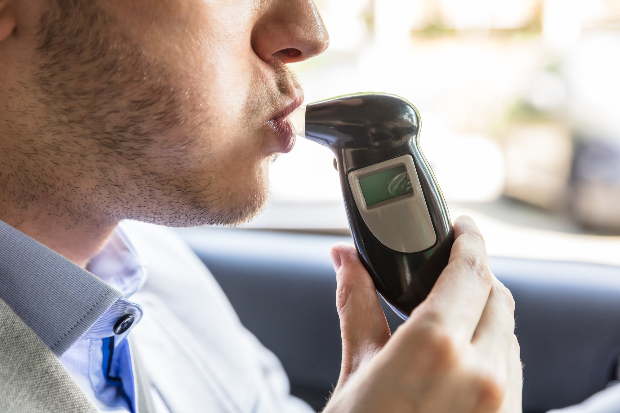Close-up of a person seated in a car, blowing into a digital alcohol breathalyzer device.