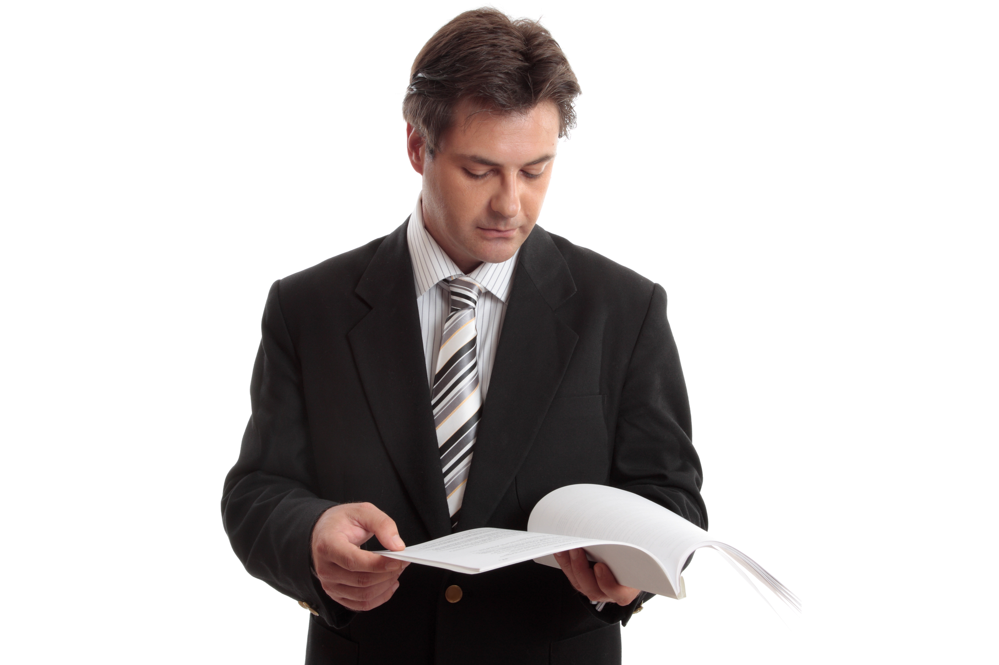An individual in a suit and tie looks through a paper report.