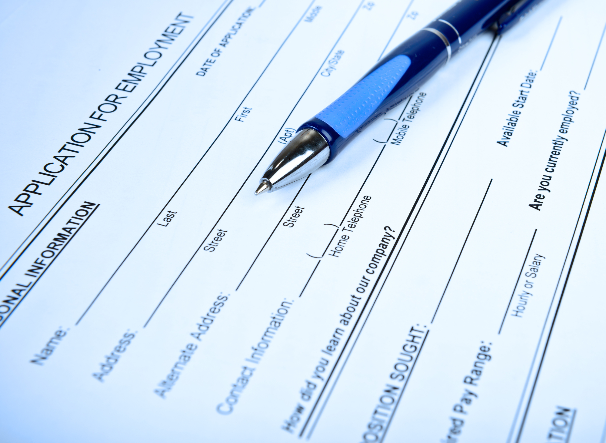 Close-up of an employment application, with a blue ballpoint pen resting on top of it.