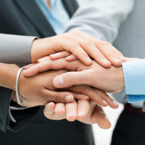 Close-up of a diverse group of workers' hands resting on top of one another in a gesture of support.