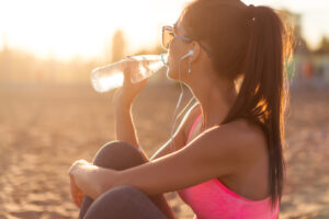 An individual in athletic apparel sitting in the sand at the beach at sunset, listening to music through earbuds and drinking bottled water.