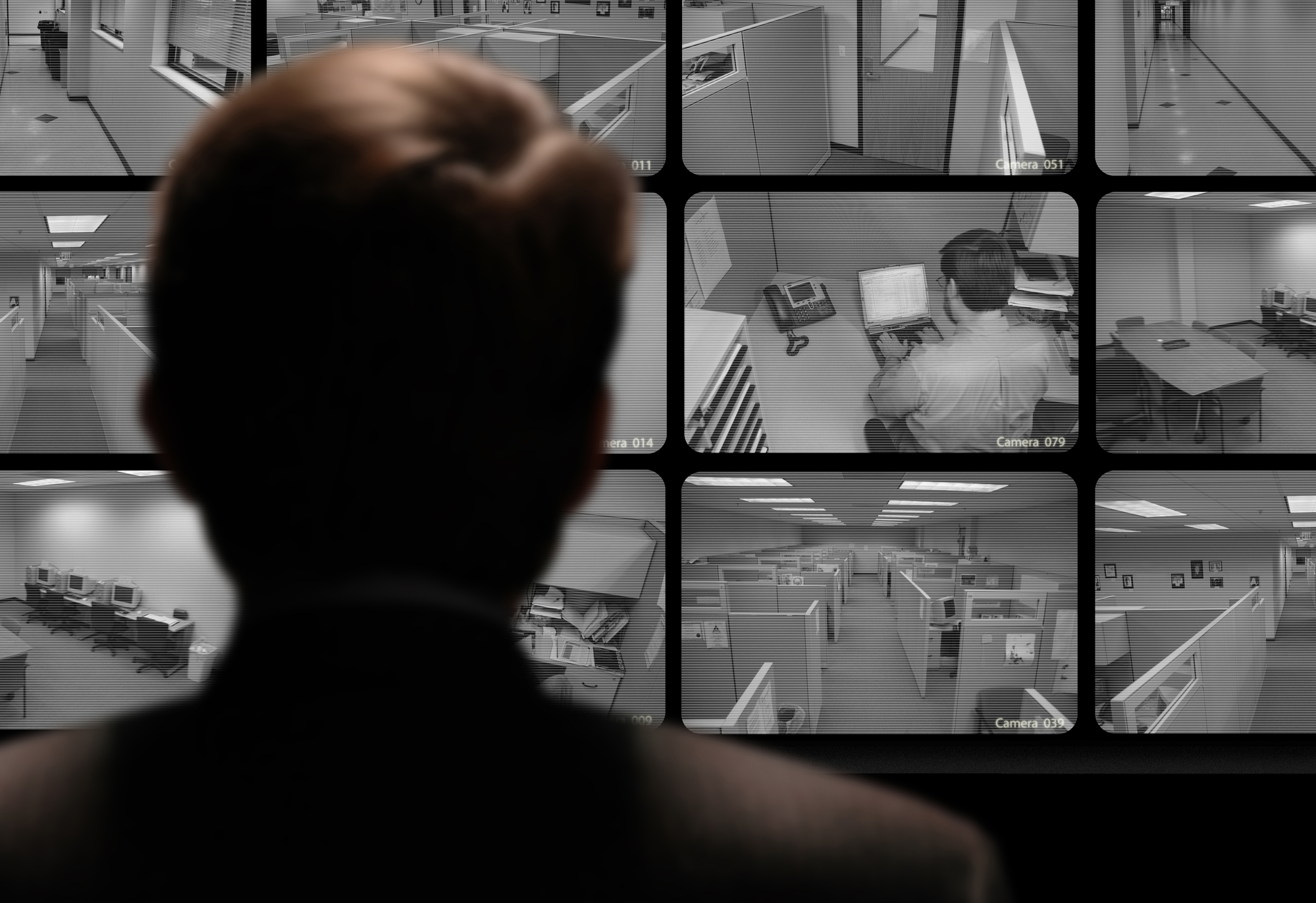 Over-the-shoulder view from behind a person in shadows observing an office via closed-circuit televisions and cameras.