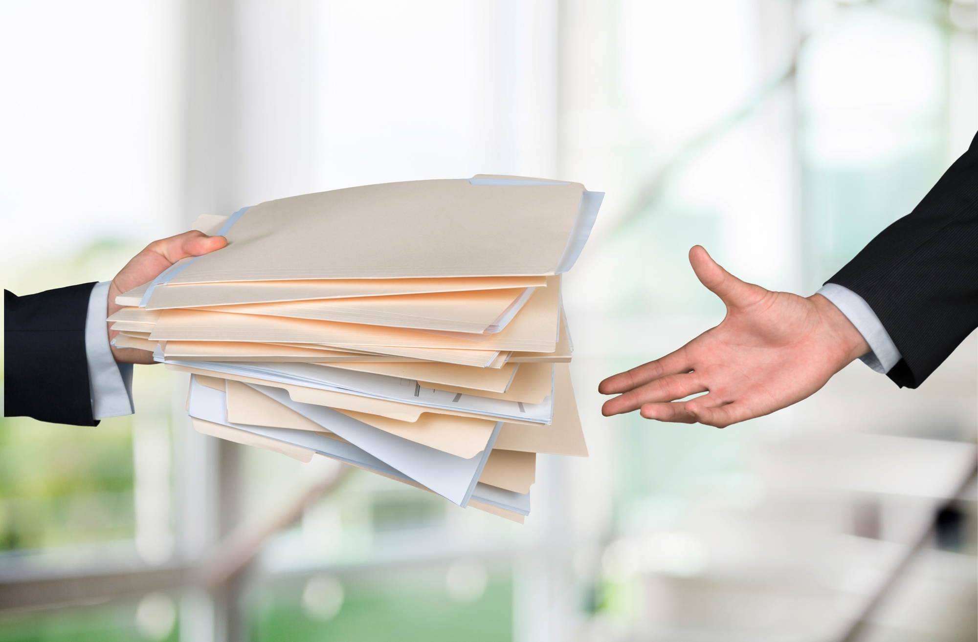 Close-up of a person's hand holding a large stack of folders, passing them to another person wearing a suit.