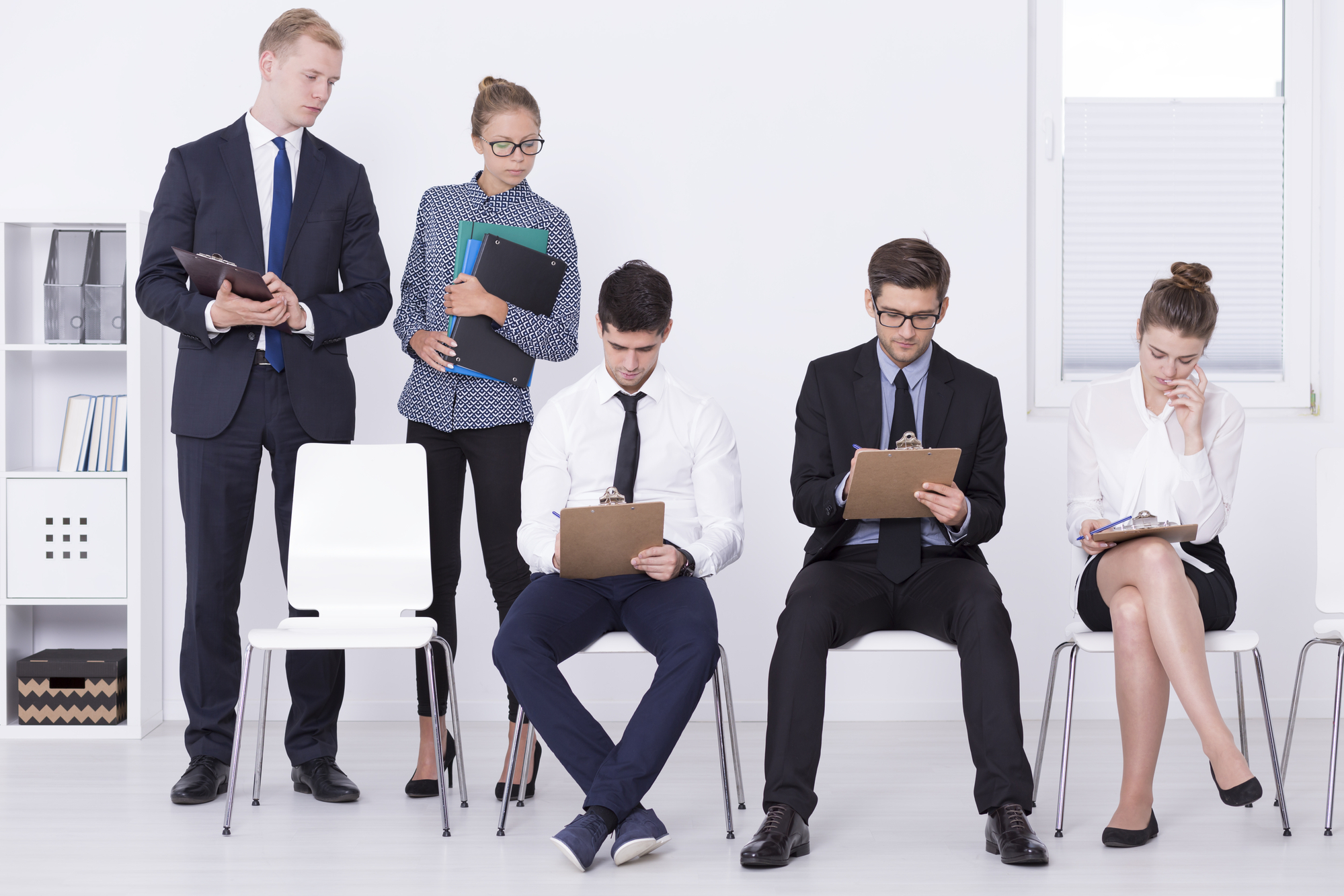 A row of individuals wearing business apparel seated and filling out forms on clipboards, while two other people watch over them.