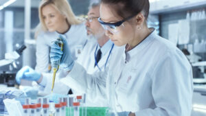 Three scientists in white lab coats and goggles working with vials and a pipette.
