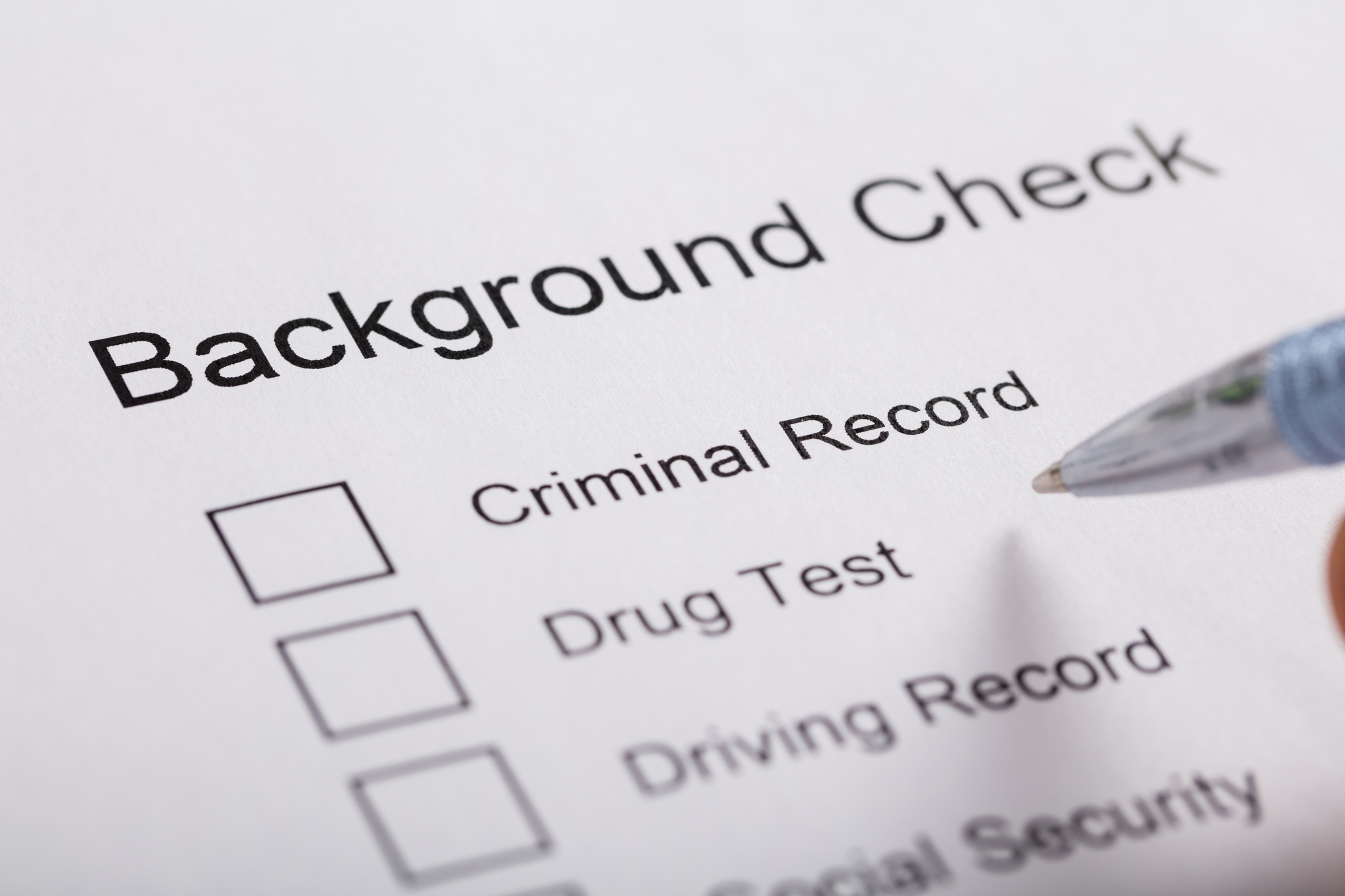 """Close-up of a ballpoint pen hovering over a document labeled """"Background Check"""" with empty checkboxes available for """"Criminal Record,"""" """"Drug Test,"""" Driving Record,"""" and """"Social Security"""" visible."""